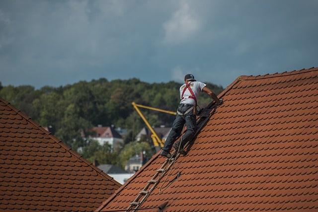 Takläggare som arbetar säkert på ett hustak